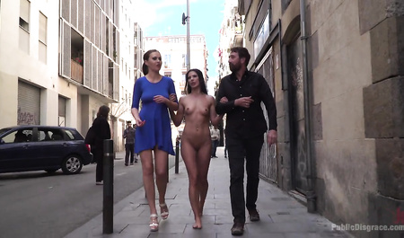 A couple walks through the city with a naked girl in the role of bottom