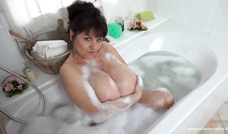 Beautiful lady with big Boobs swims in the bathtub